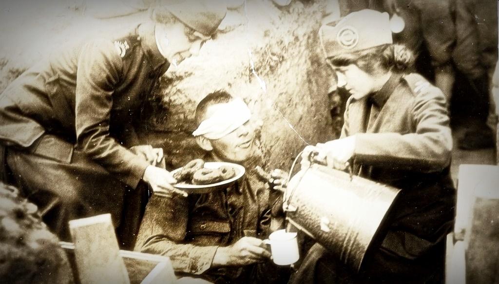 Волонтеры угощают американского солдата пончиками во времена Первой мировой войны.