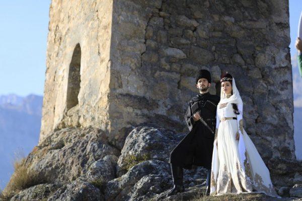 Новоиспеченные молодожены на фоне древней крепости
