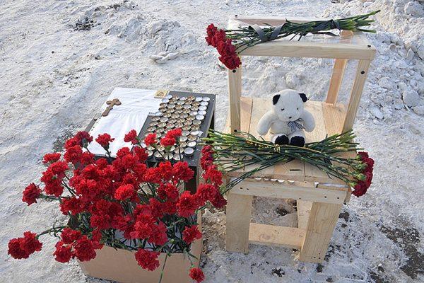 На место трагедии люди приносят много цветов