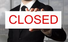 businessman in black suit holding sign closed