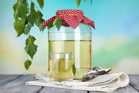 Glass and large flagon of fresh birch sap  on a wooden table on nature background