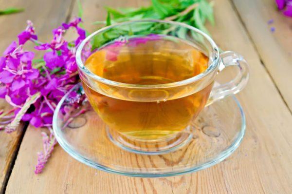 Herbal tea in glass cup of fireweed on board